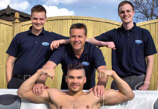 Posh Spas' Andy Hutchinson, centre and sons Nick and James pictured with school mate Louis Smith in his new Fontaine hot tub. Pic by Jules Corry.
