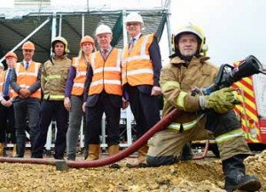 Members of Sunderland City Council and Pellikaan Construction are pictured with firefighter Bob Foster before hosing water into the new Washington Leisure centre swimming pool for the first time.